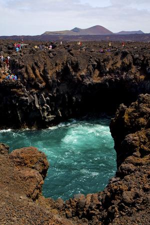 los hervideros: people   coastline stone volcanic spain  water  in lanzarote los hervideros sky cloud beach  and summer Editorial