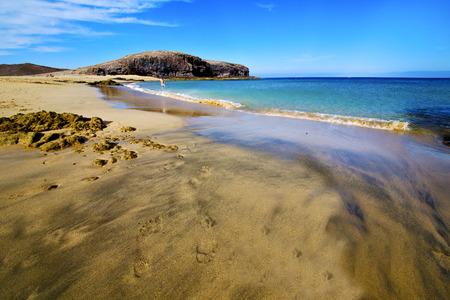footstep: footstep coast people stone volcanic spain  water in lanzarote  sky cloud beach  and summer