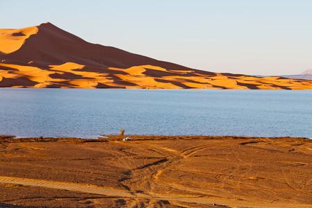 inhospitable: sunshine in the desert of morocco sand and  lake        dune Stock Photo