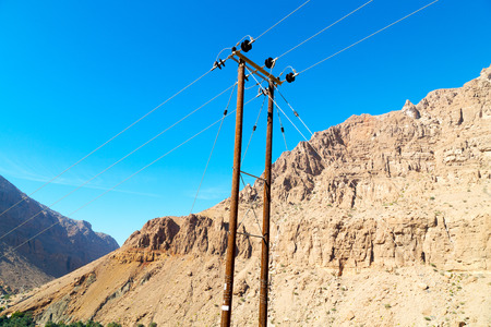 oman background: wood pylon energy and current line    in oman the electric cable
