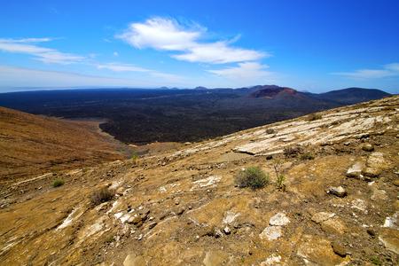 erupting: bush timanfaya  in los volcanes volcanic rock stone sky  hill and summer  lanzarote spain lagoon Stock Photo