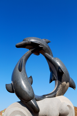 oman musact  old statue of dolphin in the sea and clear sky
