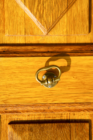 the taino rusty brass brown knocker in a  door curch  closed wood italy  lombardy Stock Photo