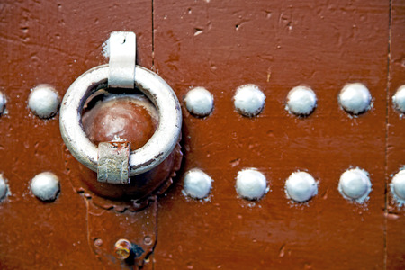 rusty nail: brown  morocco in africa the old wood  facade home and rusty safe padlock Stock Photo