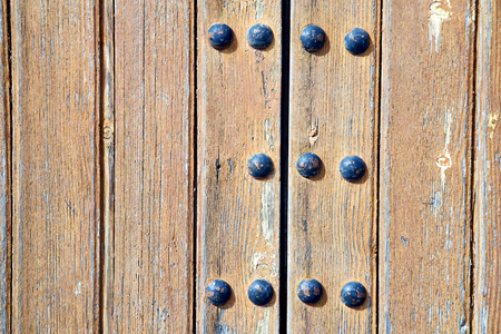 stripped: stripped paint in the blue  wood door      and rusty      nail