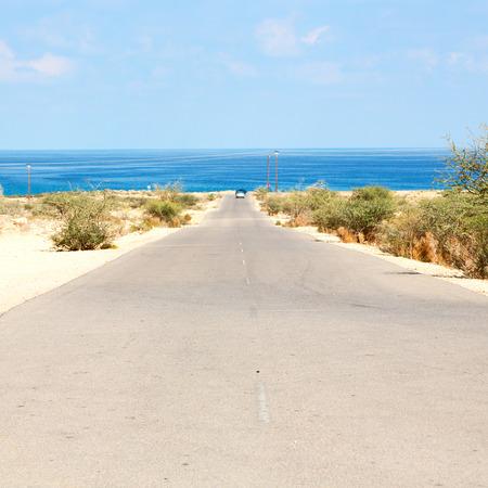 in oman old asphalt road near the coastline Stock Photo
