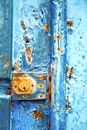 metal nail dirty     stripped paint in the brown   red wood door and rusty  knocker