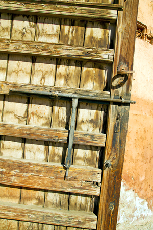 rusty nail: brown    morocco in    africa the old wood  facade home and rusty safe padlock