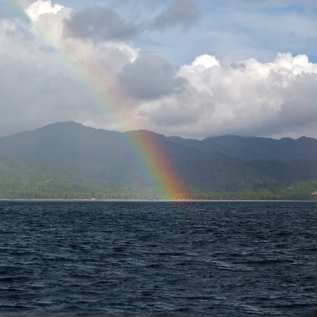 from a boat the rainbow from  ocean and island in background Stock Photo