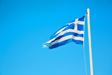 waving greece flag  in the blue sky and      flagpole Stock Photo