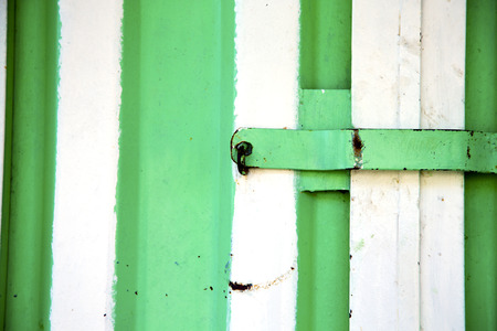 door knob: metal   green    morocco in    africa the old wood  facade home and rusty safe padlock