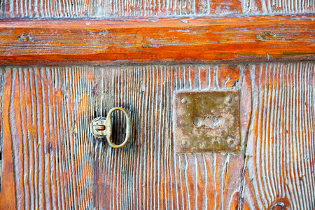 varese abstract  rusty brass brown knocker in a   closed wood door venegono italy
