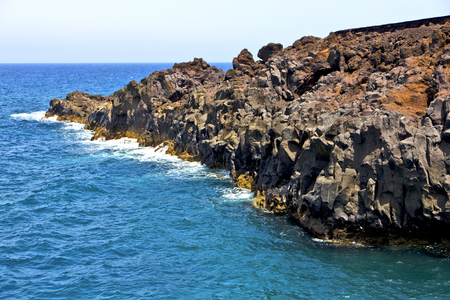 brown rock in white coast lanzarote   spain   beach  stone water  and summer hervideros