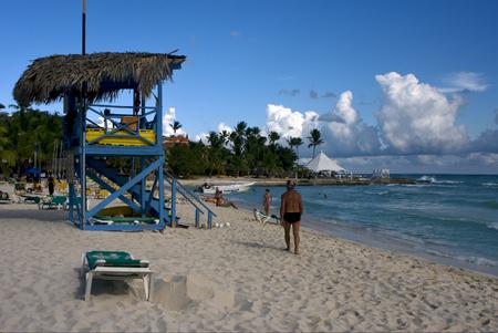 lifeguard chair cabin in republica dominicana  rock stone sky cloud people coastline and summer