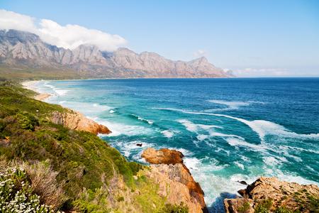 Desenfoque en Sudáfrica costa del Océano Índico cerca de la montaña y la playa con pkant y el casquillo Foto de archivo - 78159871