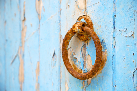 safeguards: morocco knocker in africa the old wood  facade home and rusty safe padlock