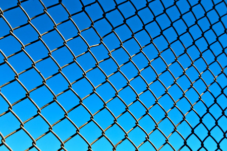 Abstract texture of a metal grid surface in the blue sky background