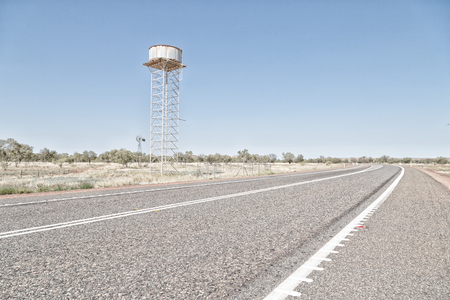In Australia the concept of remote in the outback with asphalt line and water tank