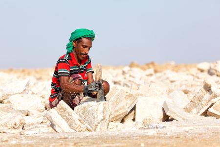 ETHIOPIA,DANAKIL-CIRCA  DECEMBER 2017--unidentified man working the block of salt