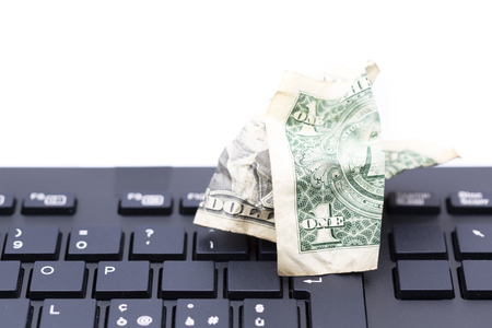 blurred crumpled dollar money background in a keyboard like concept of problem anc copy space