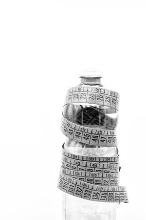 in the white light and copy space bottle of water and red measure tape like concept of lifestyle and diet Stock Photo