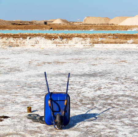 in  danakil ethiopia  africa  in the land of afar the salt flat in the white space and wheelbarrow for the worker near the hill