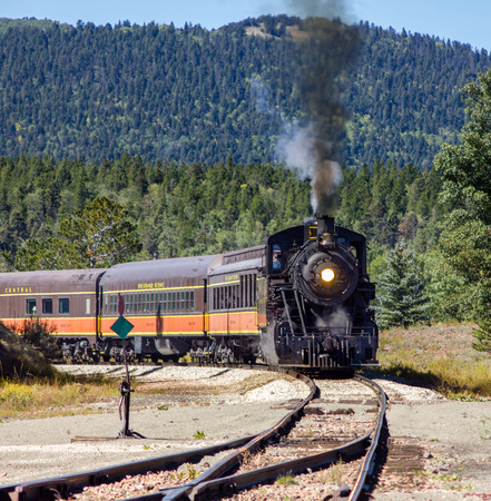 loco: steam engine passenger train rounding a bend with black smoke from stack