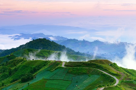 Road to top of misty hill at dawn Thailand photo
