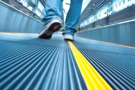 Foot move in airport escalator