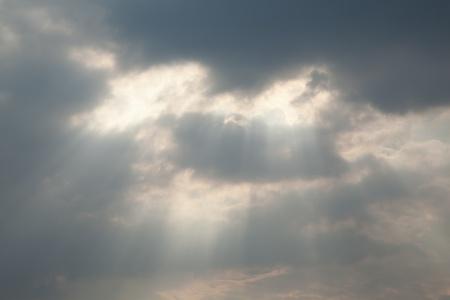 Sunbeam through cloud on gray sky photo
