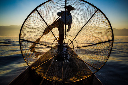 inle: Silhouette fishermen in Inle Lake at sunrise, Inle, Shan State, Myanmar Stock Photo