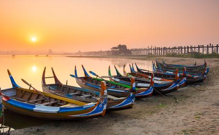 longest: Wooden boat in Ubein Bridge at sunrise, Mandalay, Myanmar (World longest wooden bridge)
