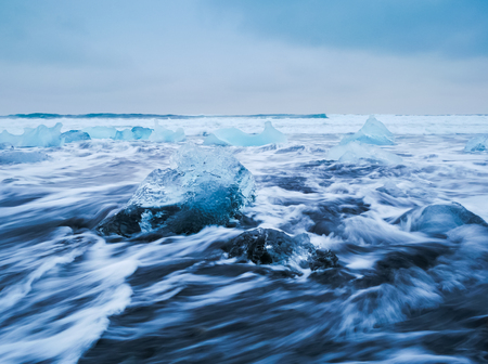 Icebergs floating on black volcanic beach, South Iceland