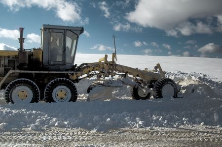 Grader removes snow from road photo