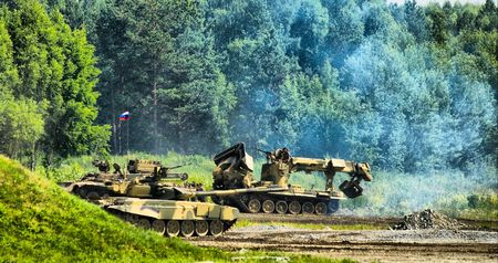 Tank T-80, engineering vehicle moving through field and forest photo
