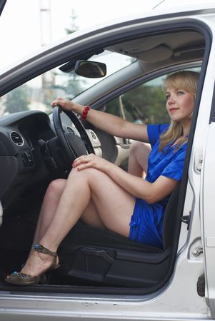 Young woman sitting in a car on the parking photo