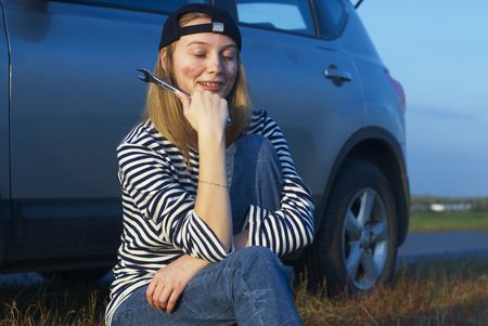 Car on roadside and young woman attempting to repair it Stock Photo - 5626904