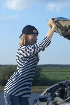 Car on roadside and young woman attempting to repair it Stock Photo - 5626902