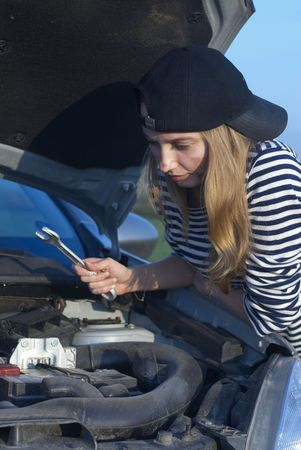 Car on roadside and young woman attempting to repair it Stock Photo - 5626906