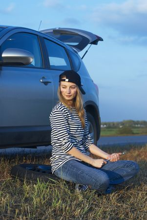Car on roadside and young woman attempting to repair it photo