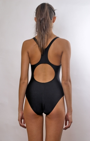 Back of young woman in swimming suit at studio photo