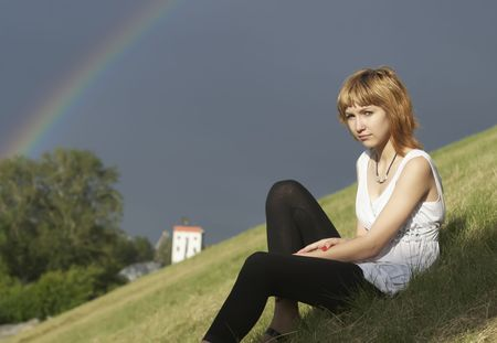 Young woman and rainbow after rain photo