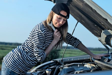 Young woman attemting to repair broken car photo