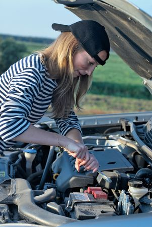 Young woman attemting to repair broken car Stock Photo - 5939731