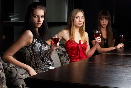 Young women sitting in cafe with wine and talking photo
