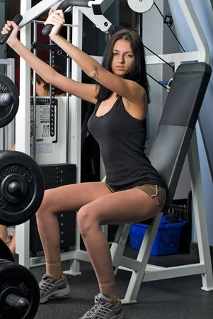 Young woman on training apparatus in fitness center photo