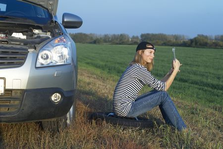Frustrating young woman with wrench near broken car photo