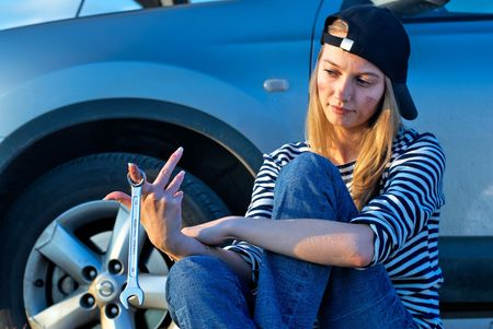 Frustrating young woman with wrench near broken car