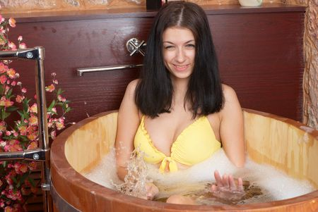 Woman sitting in wooden bath at japanese sauna photo