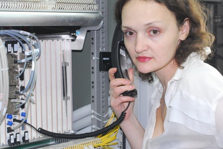 Woman working on technical site of mobile switching center for connection cellular phones photo